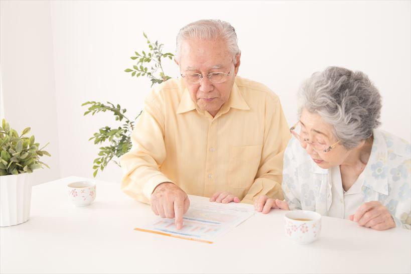 チラシを熱心に見る老夫婦